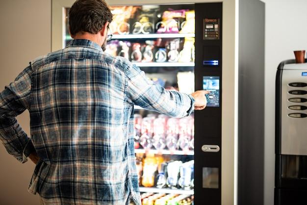 Rückansicht eines erwachsenen, reifen mannes, der snacks und getränke auf einem kostenlosen 24-stunden-automaten auswählt - leute, die lebensmittel am flughafen-gate kaufen - reiselebensstil und ungesunde ernährung