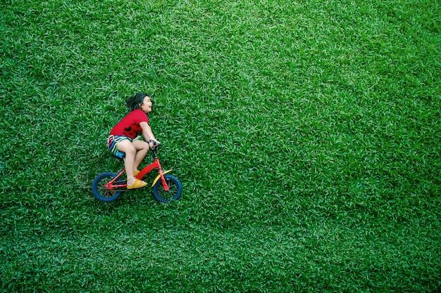 Rückansicht eines glücklichen asiatischen kinder. mädchen auf fahrrad legen am grünen rasen am sommertag nieder