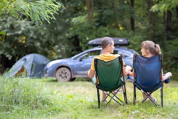 Rückansicht eines glücklichen paares, das auf stühlen am campingplatz sitzt, der zusammen entspannt. reise-, camping- und urlaubskonzept.