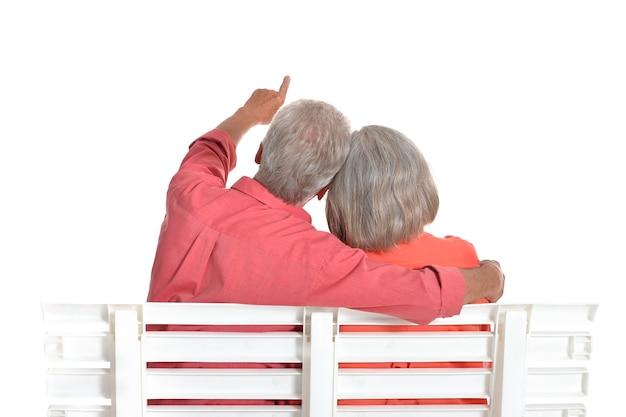 Rückansicht eines glücklichen seniorenpaares, das auf einer bank auf weißem hintergrund sitzt