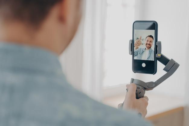 Rückansicht eines gutaussehenden lächelnden jungen brünetten mannes mit stoppeln, der zu hause selfie auf dem smartphone mit gimbal-stabilisator macht und ein okay-zeichen zeigt, trägt freizeitkleidung blogging-konzept