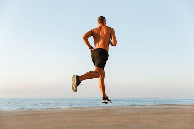 Rückansicht eines hemdlosen sportlers mit laufenden kopfhörern