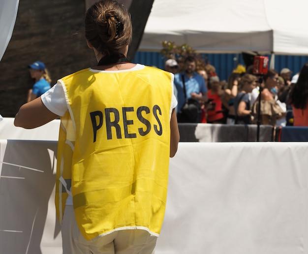 Rückansicht eines journalisten mit kamera in gelber weste mit presseschild