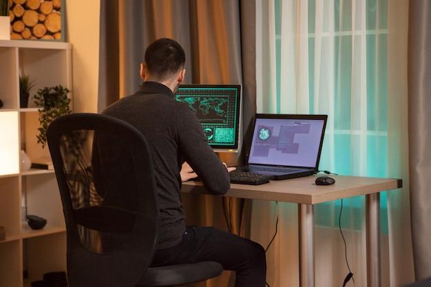Rückansicht eines jungen hackers, der nachts einen virus auf dem laptop eintippt.