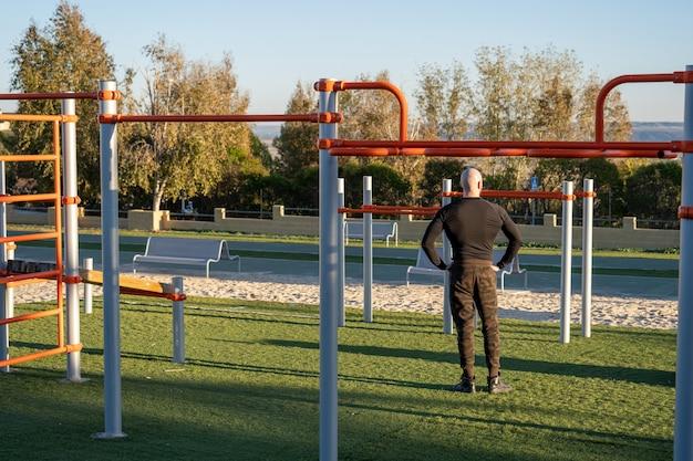 Rückansicht eines jungen hispanischen mannes, der sich nach dem training auf dem sportplatz ausruht