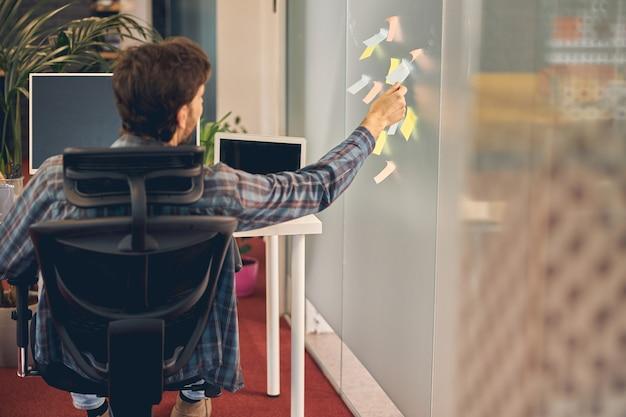 Rückansicht eines jungen mannes, der eine klebrige papiernotiz an der wand liest, während er bei der arbeit im stuhl sitzt