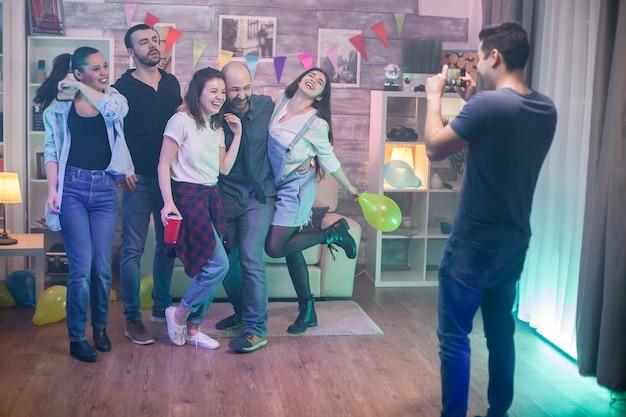 Rückansicht eines jungen mannes, der gerne fotos von engen freunden auf einer party in einer wohnung macht.