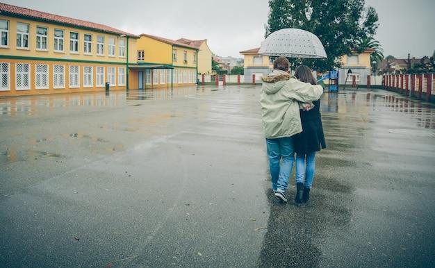 Rückansicht eines jungen paares, das sich unter dem regenschirm an einem regnerischen herbsttag umarmt. liebes- und paarbeziehungskonzept.