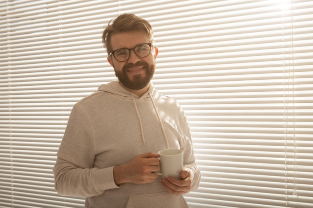 Rückansicht eines jungen, stilvollen mannes mit bart und kaffee, der durch das loch in den jalousien späht und auf die straße blickt. morgensonne und positivität genießen