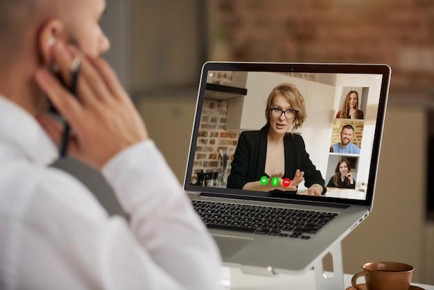 Rückansicht eines kahlen männlichen angestellten, der seinen rechten kopfhörer während einer videokonferenz überprüft.