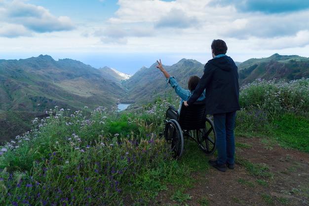 Rückansicht eines liebevollen paares, junger mann mit seiner behinderten freundin oder frau im rollstuhl, die zusammen auf einem berghügel eine atemberaubende naturlandschaft genießen. reisen mit körperlichen behinderungen