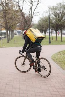 Rückansicht eines lieferboten mit thermorucksack, der fahrrad während der arbeit fährt