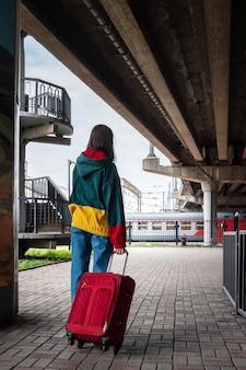 Rückansicht eines mädchens in hellen kleidern mit einem koffer, der am bahnhof zum zug geht. ein mädchen fährt mit dem zug in den urlaub, auf eine reise, in den urlaub. reisen mit dem zugkonzept