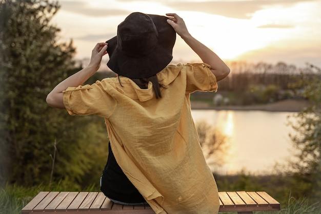 Rückansicht eines mädchens mit hut, das den sonnenuntergang auf einer bank im wald genießt.