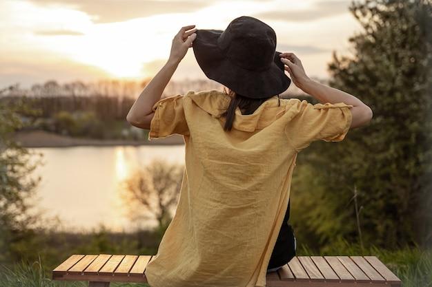 Rückansicht eines mädchens mit hut, das den sonnenuntergang auf einer bank im wald genießt