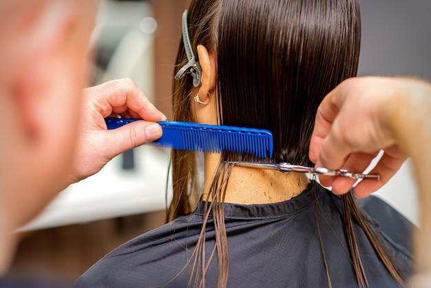Rückansicht eines männlichen friseurs schneidet haare der jungen frau mit siscors und kamm
