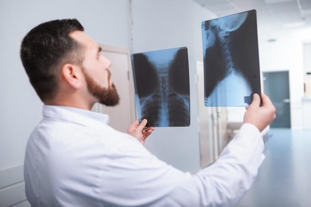 Rückansicht eines männlichen praktizierenden, der zwei röntgenaufnahmen der wirbelsäule eines patienten vergleicht