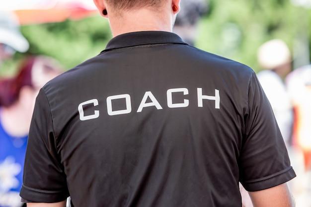 Rückansicht eines männlichen trainers, der schwarzes trainerhemd mit dem weißen wort coach auf der rückseite gedruckt trägt
