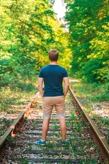 Rückansicht eines mannes, der auf einer verlassenen bahnstrecke im wald steht