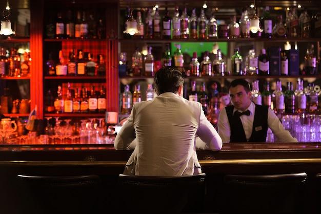 Rückansicht eines mannes, der einem barkeeper ein getränk bestellt