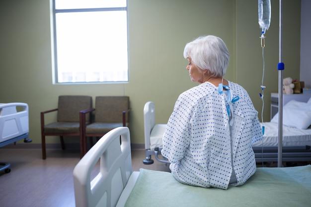 Rückansicht eines nachdenklichen älteren patienten, der auf dem bett sitzt