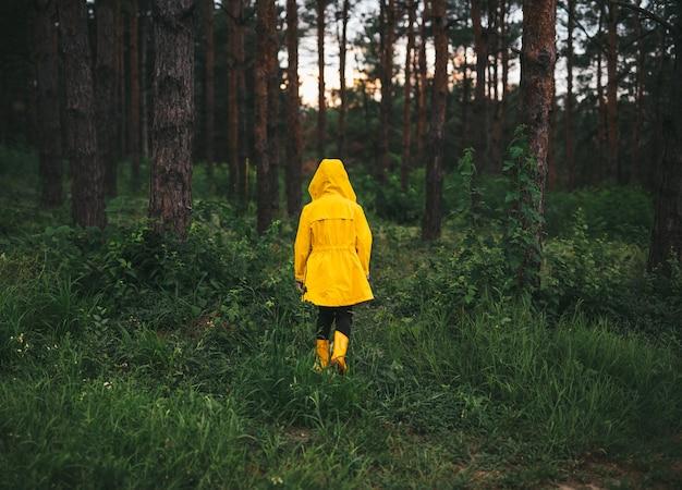 Rückansicht eines nicht erkennbaren kindes in gelbem regenmantel und gummistiefeln, das am sommerabend allein im grünen wald spaziert