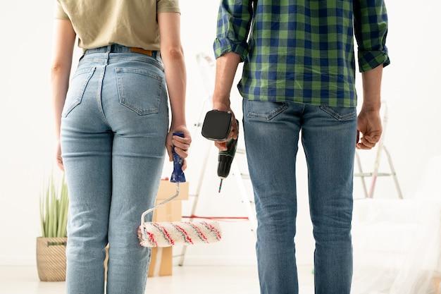 Rückansicht eines nicht erkennbaren paares in jeans, die mit farbroller und akkuschrauber stehen, während sie bereit sind, den raum zu wechseln