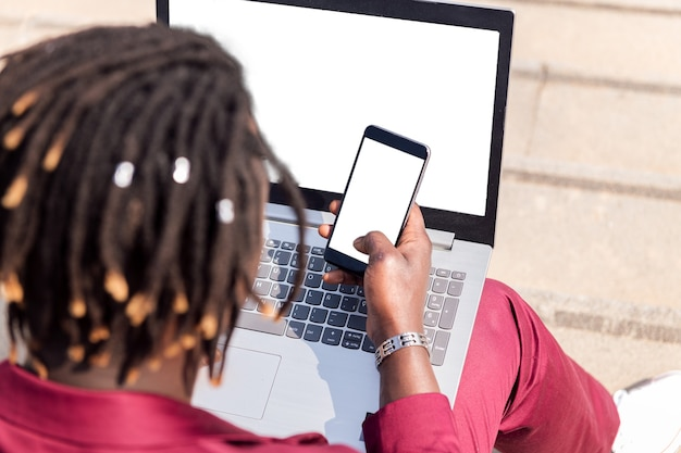 Rückansicht eines nicht erkennbaren schwarzen geschäftsmannes mit smartphone und computer-laptop, technologie- und fernarbeitskonzept, platz für text kopieren