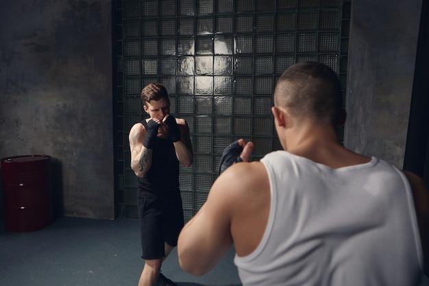 Rückansicht eines nicht wiedererkennbaren männlichen kämpfers mit breiten muskulösen schultern, der gegen jungen kaukasischen kerl mit tätowierungen kämpft, die schwarzes outfit und verbände tragen. sport, kampfkunst und wettkampf