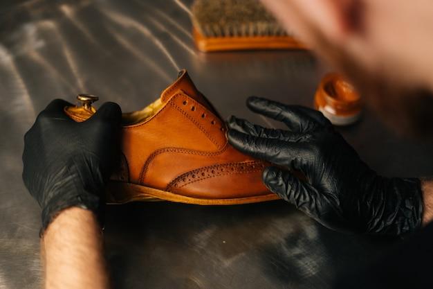 Rückansicht eines nicht wiederzuerkennenden schusters in schwarzen handschuhen, der farbe auf hellbraune lederschuhe mit ...