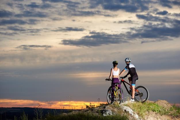 Rückansicht eines paares, das ein mountainbike oben fährt und den sonnenuntergang und einen schönen abend in den bergen genießt.
