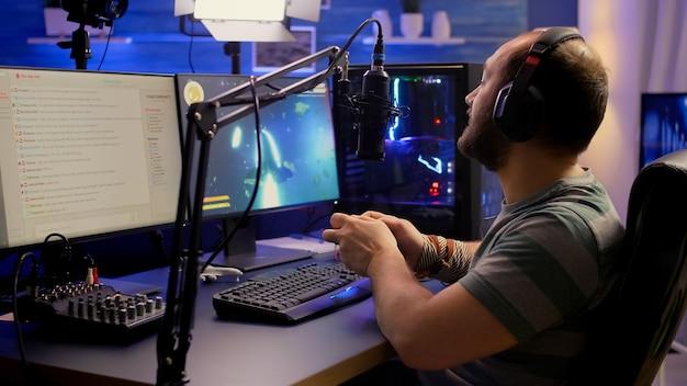 Rückansicht eines pro-streamers, der grafik-cyber-space-shooter-videospiele mit drahtlosem joystick spielt playing