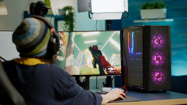 Rückansicht eines pro-streamers mit kopfhörer, der fps-videospiele während eines esport-wettbewerbs mit einem leistungsstarken rgb-computer spielt. spieler sitzt auf gaming-stuhl mit streaming-geräten spät in der nacht im heimstudio