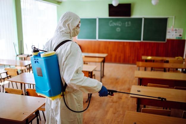 Rückansicht eines professionellen sanitärarbeiters, der das klassenzimmer vor beginn des akademischen jahres desinfiziert. ein mann im schutzanzug reinigt das auditorium vom coronavirus covid-19. gesundheitsvorsorge.