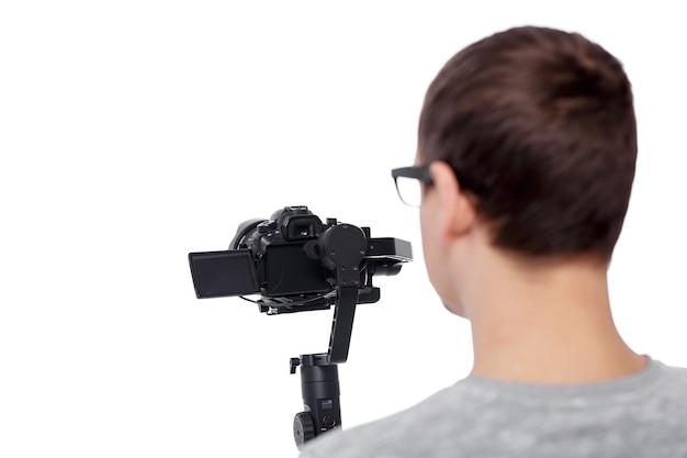 Rückansicht eines professionellen videofilmers, der videos mit einer dslr-kamera auf einem gimbal-stabilisator auf weißem hintergrund aufnimmt