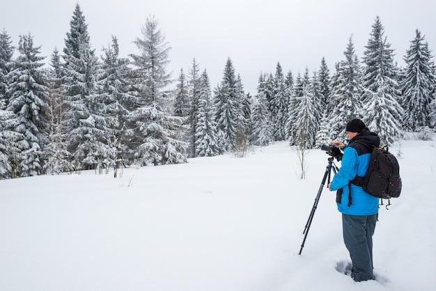 Rückansicht eines reisenden fotografen, der einen verschneiten wald fotografiert, der in einer schneeverwehung und im nebel an einem frostigen wintertag steht