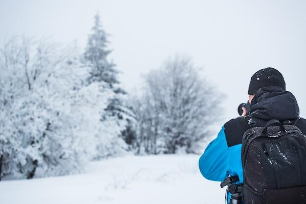 Rückansicht eines reisenden fotografen, der einen verschneiten wald fotografiert