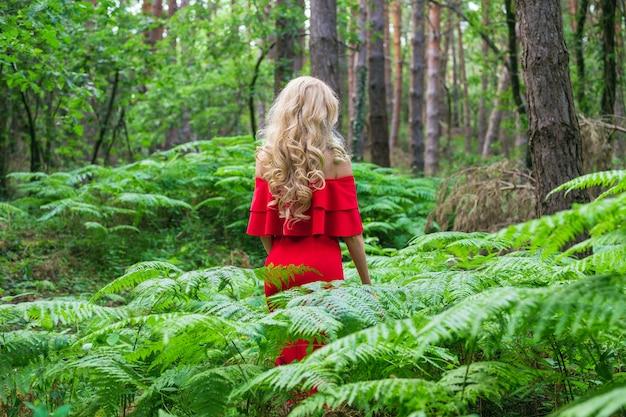 Rückansicht eines schönen blonden mädchens in einem schicken roten kleid, das einen farn im feenwald berührt. atmosphäre fantastisch.