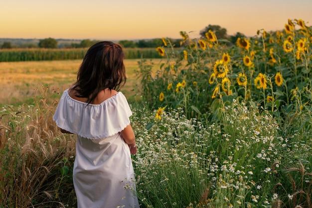 Rückansicht eines schönen frauenporträts auf einem sommerfeld bei sonnenuntergang