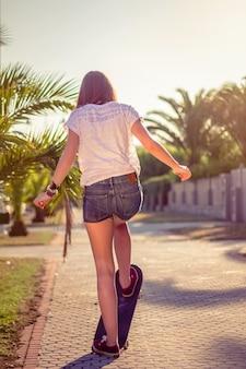 Rückansicht eines schönen jungen mädchens mit kurzen hosen, das im sommer draußen auf einem skateboard fährt. ausgabe mit warmen tönen.