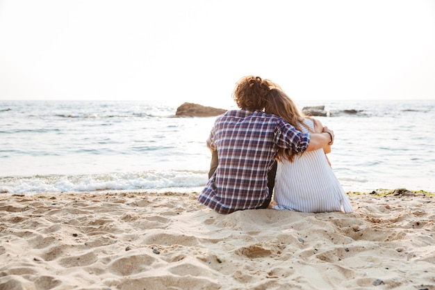 Rückansicht eines schönen jungen paares, das am strand sitzt und umarmt