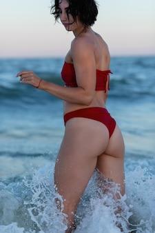 Rückansicht eines sexy tätowierten jungen mädchens in einem roten badeanzug, der am strand aufwirft. schöne blonde frau mit langen haaren entspannt sich am meer. das konzept eines sportmodells, bademode