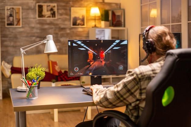 Rückansicht eines spielers, der spät in der nacht im wohnzimmer einen shooter auf seinem leistungsstarken pc-computer spielt.
