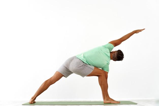 Rückansicht eines sportlichen mannes, der yoga im yoga-kurs praktiziert und sich zurückstreckt