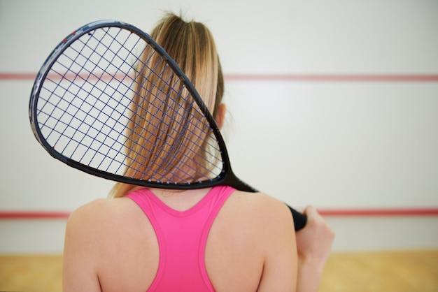 Rückansicht eines squash- oder tennisspielers mit schläger