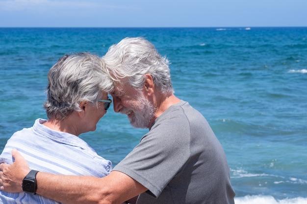 Rückansicht eines verliebten seniorenpaares, das am strand sitzt und sich ansieht. zwei rentner genießen sommerferien und freiheit
