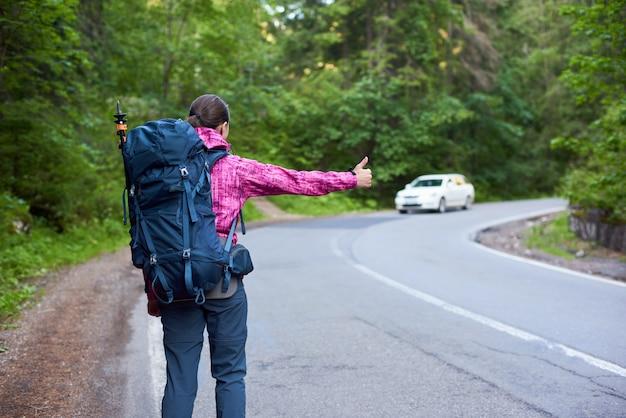 Rückansicht eines weiblichen reisenden mit einem rucksack, der ein auto auf der straße kathicng