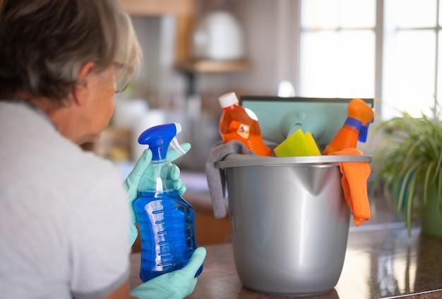 Rückansicht eines weiblichen volkes, das für die hausarbeit bereit ist, während sie einen grauen plastikeimer mit reinigungsartikeln in den händen hält. helles licht aus dem fenster