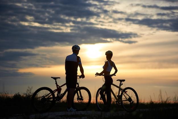 Rückansicht einiger radfahrer, die mit fahrrädern stehen und den sonnenuntergang genießen. perfekter himmel mit wolken und abendsonne