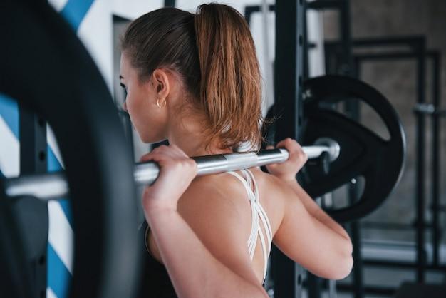 Rückansicht. foto der herrlichen blonden frau im fitnessstudio zu ihrer wochenendzeit